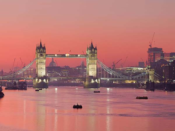 Rio Tâmisa ao anoitecer com céu avermelhado pelo por-do-sol e reflexo em suas águas